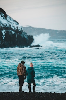 Couple standing on rock formation near body of water during daytime