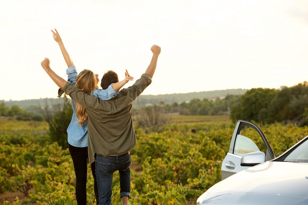 Couple standing on side of road with arms outstretched