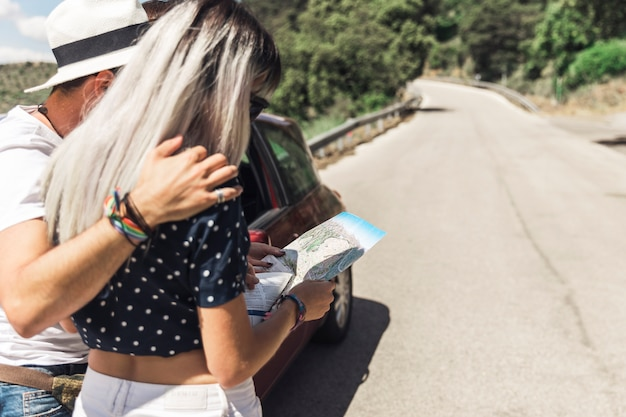 Couple standing on straight road looking at map