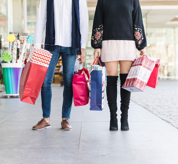 Couple standing on street with shopping bags