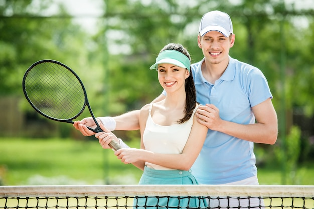 Couple standing on tennis court, holding tennis racket.