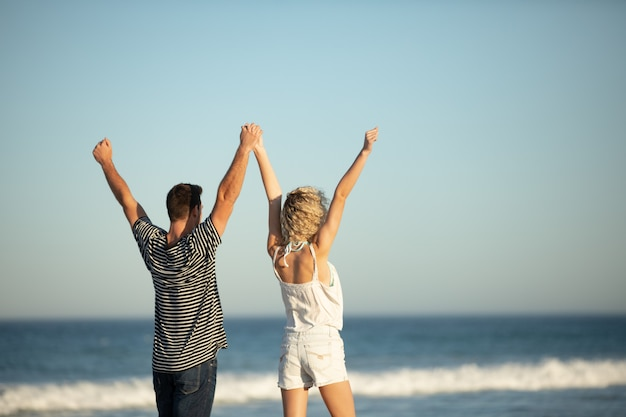 Couple standing together with arms up on the beach