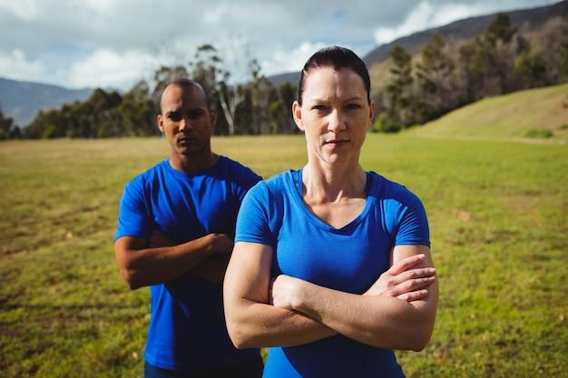 ブートキャンプのトレーニング中に腕を組んで立っているカップル