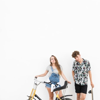 Couple standing with bicycle and skateboard on white background