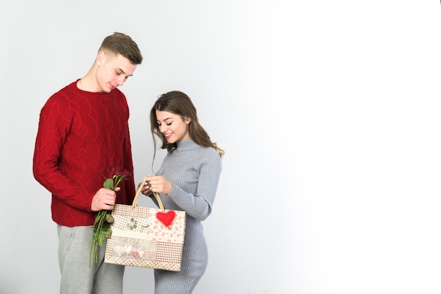 Couple standing with gift bag and flowers