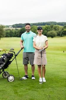 골프 코스에서 골프 클럽과 가방으로 서 커플