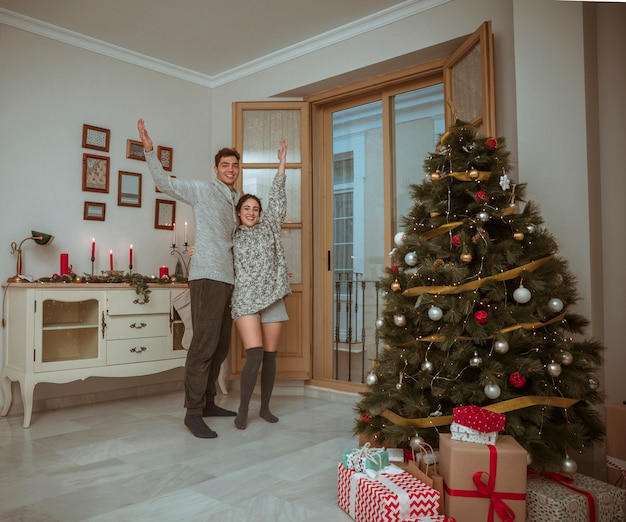 Couple standing with hands up near christmas tree