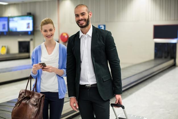空港の待合室で荷物を持って立っているカップル
