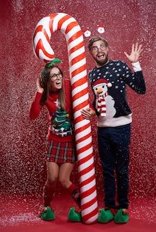 赤と白のクリスマスの杖で立っているカップル