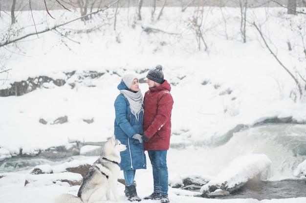 雪の冬にシベリアンハスキーと立っているカップル。滝。バレンタインデー。降雪。幸せな家族。犬。手をつないで。高品質の写真
