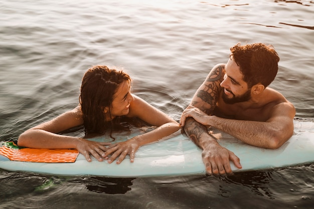 Couple standing with surfboard in sea