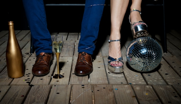 Couple standing on wooden floor with disco ball and champagne
