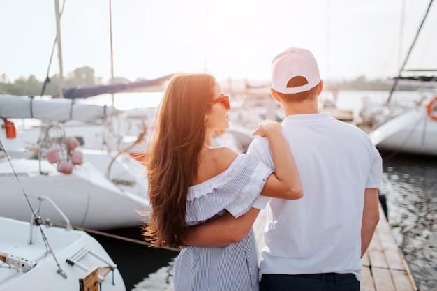 Пара стоит и смотрит на яхты, которые стоят на каждом соде от пирса.