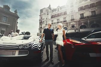 Couple stands between Bugatti and Lamborgini somewhere in Monte Carlo