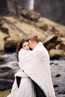 カップルは羊毛の毛布の下で山の川の岸に立っています