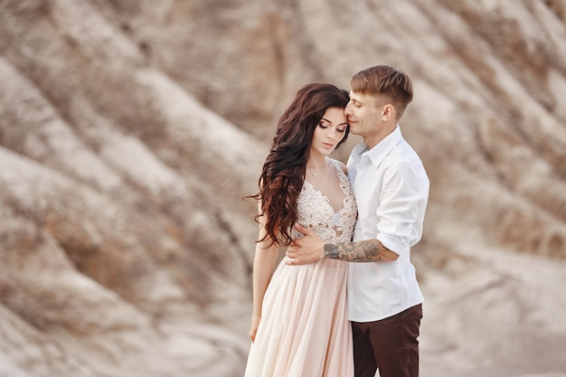 Couple stands on the precipice of the mountain and the red lake and hugging