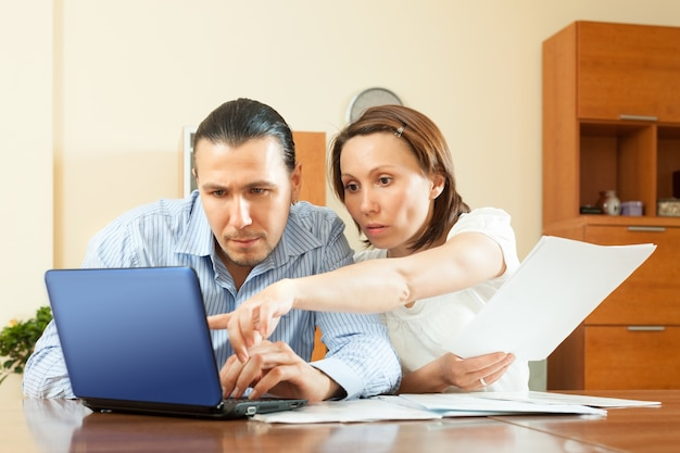Couple staring financial documents in home
