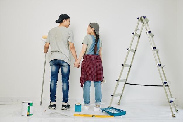 Пара, начинающая рисовать стену