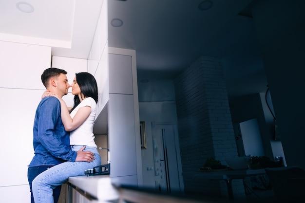 家にいるカップルが台所のテーブルに座っている女性を抱きしめます