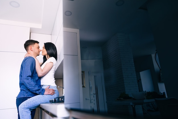 Couple staying at home hugs together woman sitting at kitchen table