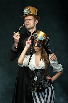 The couple steampunk. a man with a pipe and a woman with glasses and hat.