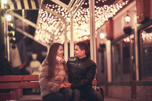 Couple at the street before christmas time. bokeh lights decorations backdrop