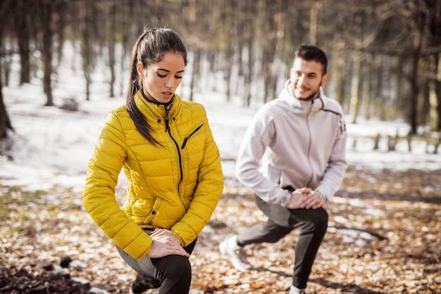 足を伸ばして、自然の中で走る前にウォーミングアップするカップル。冬と寒い天気。