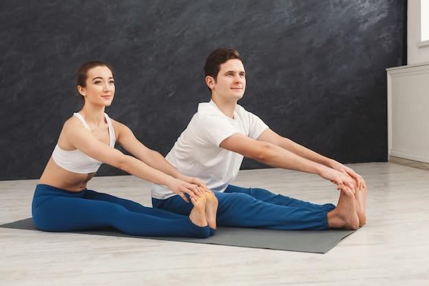 커플 스트레칭 다리, 훈련, 실내 매트에 앉아. 에어로빅과 요가 운동을 하는 젊은 남녀, 복사 공간