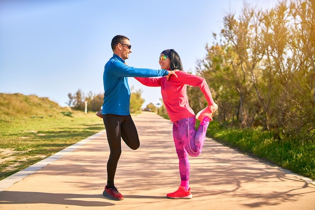 Couple stretching their legs before training, holding to each other. the woman wears bright pink and purple clothes. man is wearing blue shirt and black long trousers