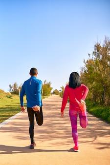 トレーニング前に足を伸ばすカップル。女性は明るいピンクと紫の服を着ています。男は青いシャツと黒い長ズボンを着ています。