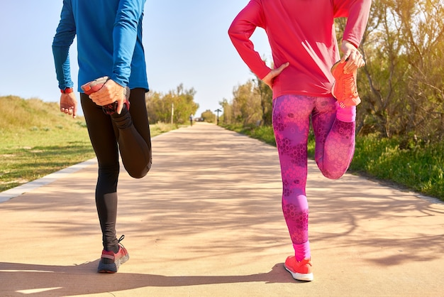 Couple stretching their legs before training. the woman wears bright pink and purple clothes. man is wearing blue shirt and black long trousers