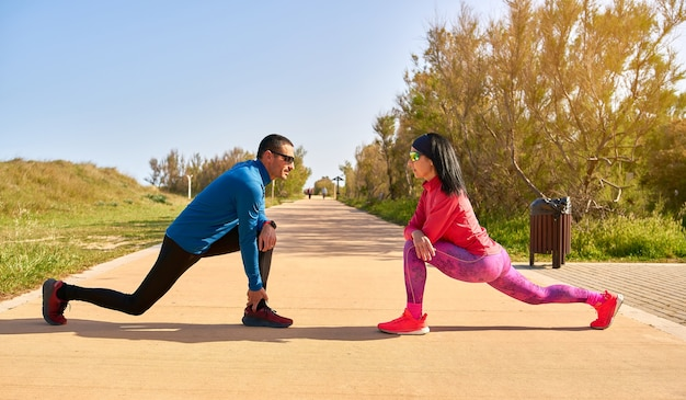 Couple stretching their legs before training. the woman wears bright pink and purple clothes. man is wearing blue shirt and black long trousers.