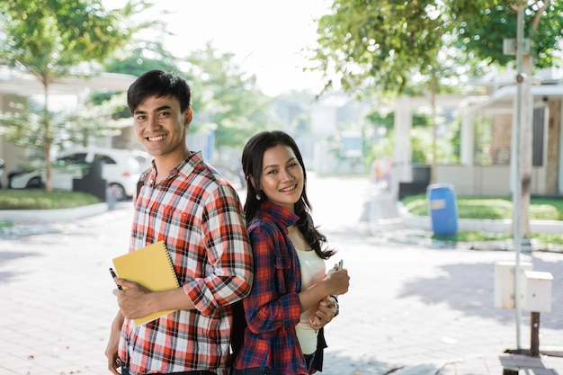 Couple student standing back to back