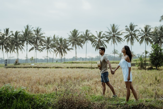 Couple stylish walking in rice field together Premium Photo