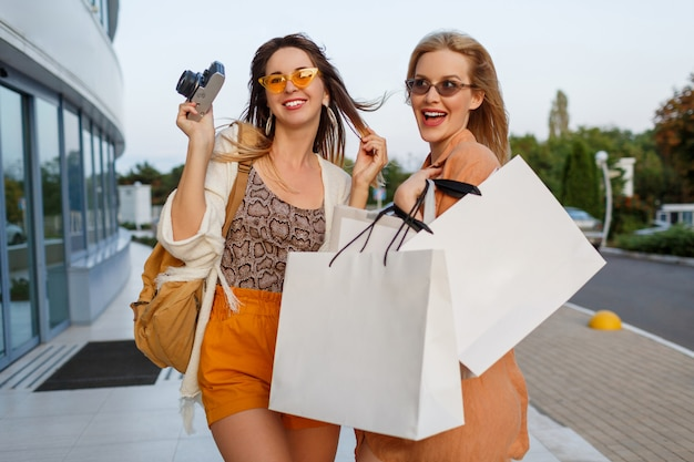 Couple of stylish women after exiting trip and shopping posing outdoor near airport