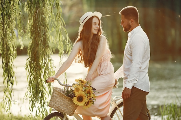 Couple in a summer park. people with vintage bicycle. girl in a hat.