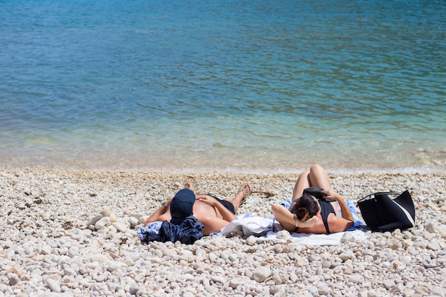 A couple sunbathes on a pebble beach near the water