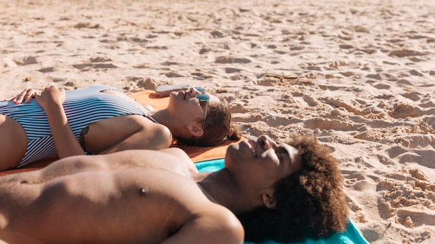 Couple sunbathing on sand