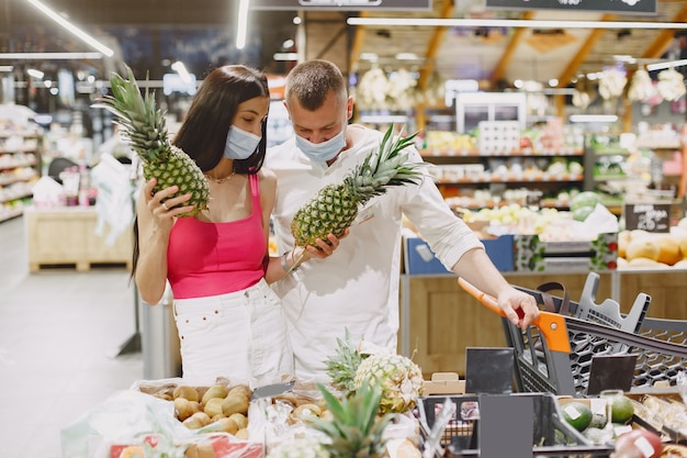 Couple in a supermarket. lady in a medical mask. people makes parchases.