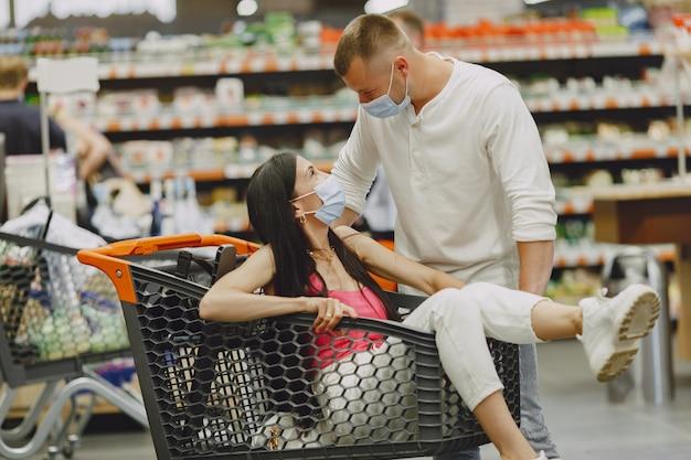 Coppia in un supermercato. signora in una maschera medica. la gente fa acquisti.