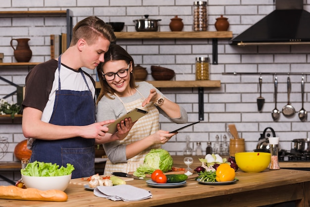 Couple surfing tablet and cooking together