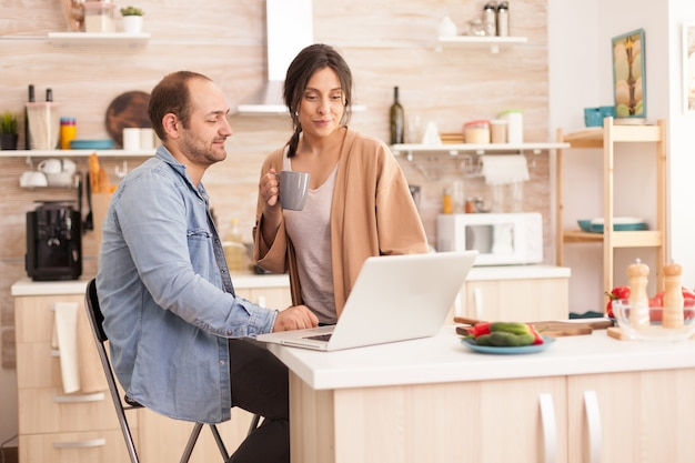 Couple surfing on web using laptop in kitchen. happy loving cheerful romantic in love couple at home using modern wifi wireless internet technology