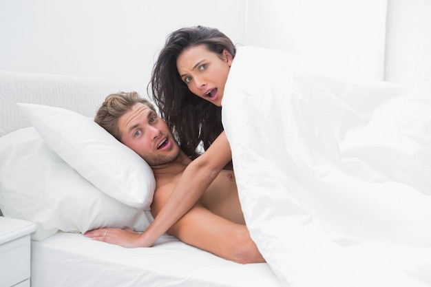 Couple surprised in bed