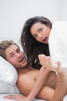 Couple surprised in their bed