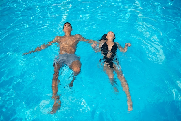 Couple in the swimming pool on turquoise water at vacation