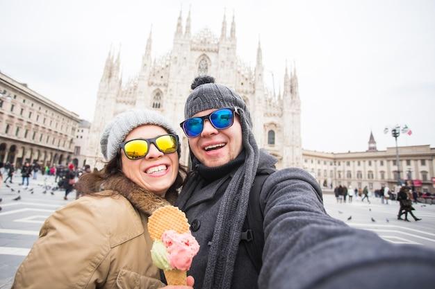 Пара делает селфи-фото с мороженым перед миланским собором дуомо.
