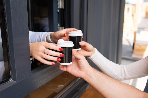 カップルは持ち帰り用のコーヒーを飲みます。休憩して外に出てください。屋外の日付。