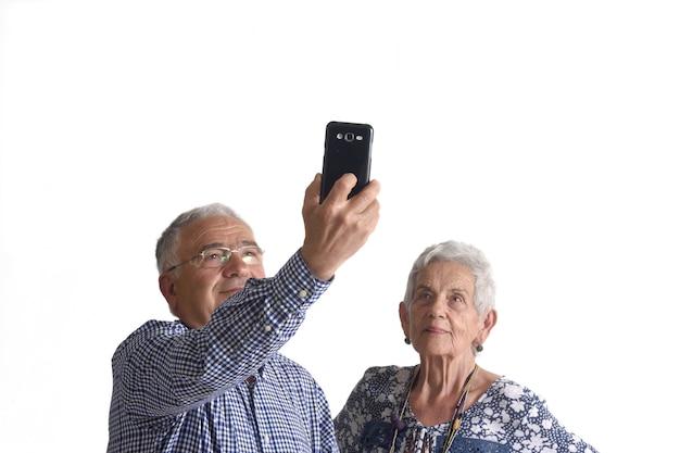白い背景の上の電話でselfieを取るカップル