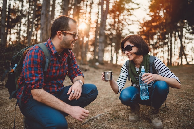 Couple taking a brake after hiking to drink a water