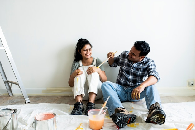 Couple taking a break from painting the walls